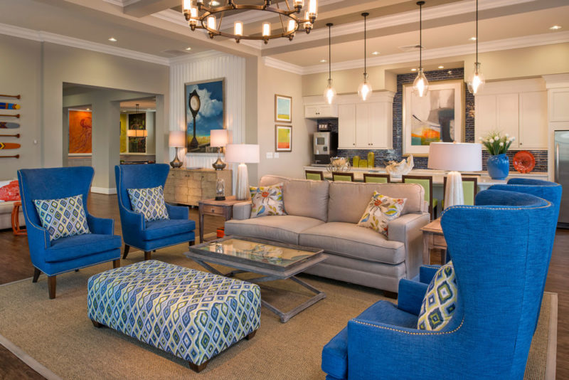 Sitting area in clubhouse merchandised with bright blue wingback chairs and beachy accessories in Delaware.