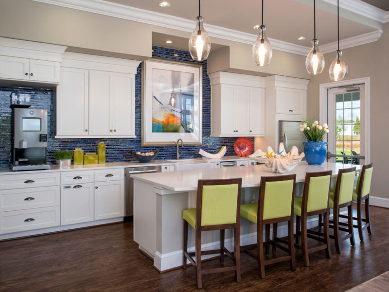Kitchen area in clubhouse with white cabinetry, blue tile backsplash and merchandised with mint green chairs in Delaware.