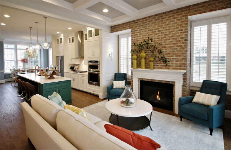 Open floor plan model home in Maryland merchandised with an accent brick wall, fireplace, and classic kitchen.