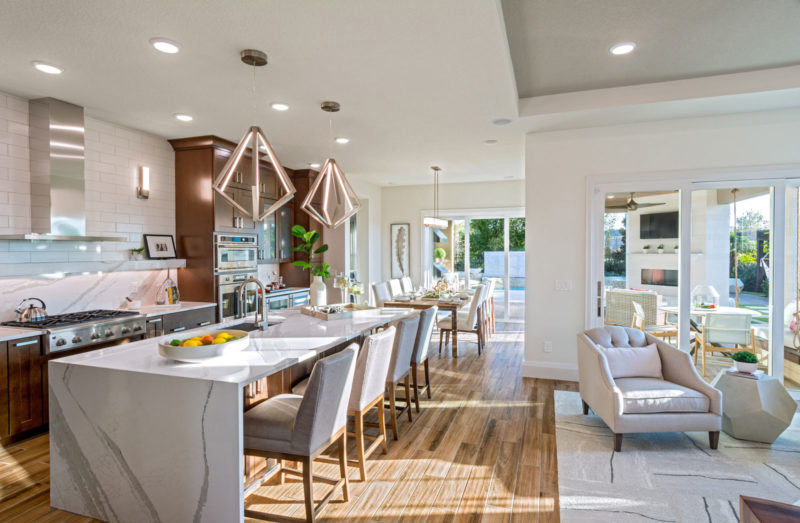 Award winning 55+ model home kitchen with and open floorplan, unique white backsplash, and hardwood floors in Florida.