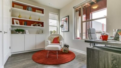 Interior design maximizing small space with white walls and red accents