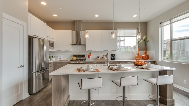 Modern model townhome white kitchen with moden cabinets and hardwood floors