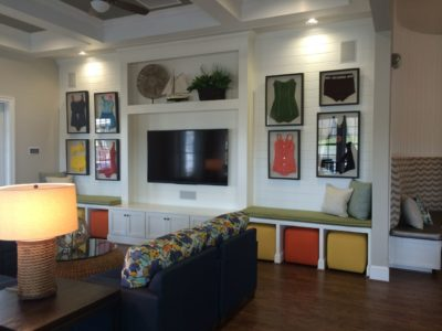 Multifamily clubhouse interior designed with framed vintage swimsuits and bright colors.