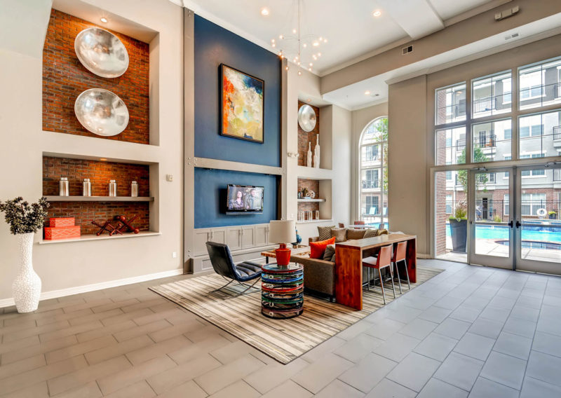 Open, bright sitting area with blue accent walls, built-ins with exposed brick in multi-family clubhouse in Colorado.