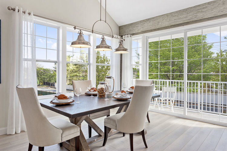 Cream dining room surrounded by windows bringing the indoor to outdoors