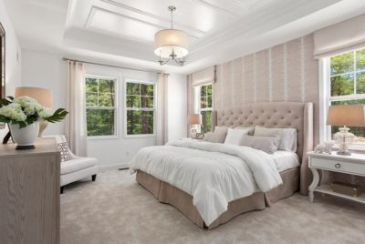 Master bedroom in model home with vaulted crown molding ceiling and cream/white finishes