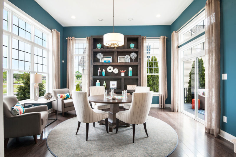 Model home flex space with dramatic turquoise accent walls and dark wood built ins, in Glassboro, New Jersey.