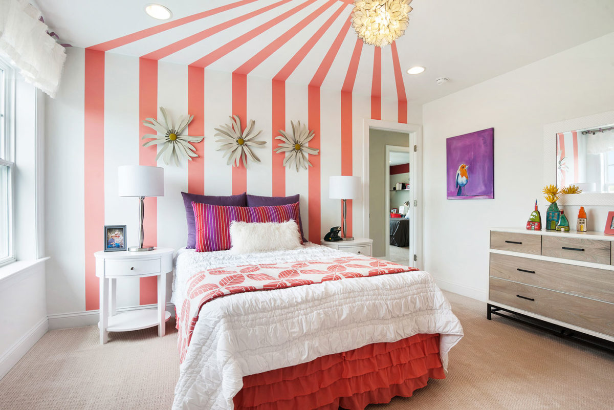 Girls room in model home enhanced with a coral striped colored accent wall, in Glassboro, New Jersey.