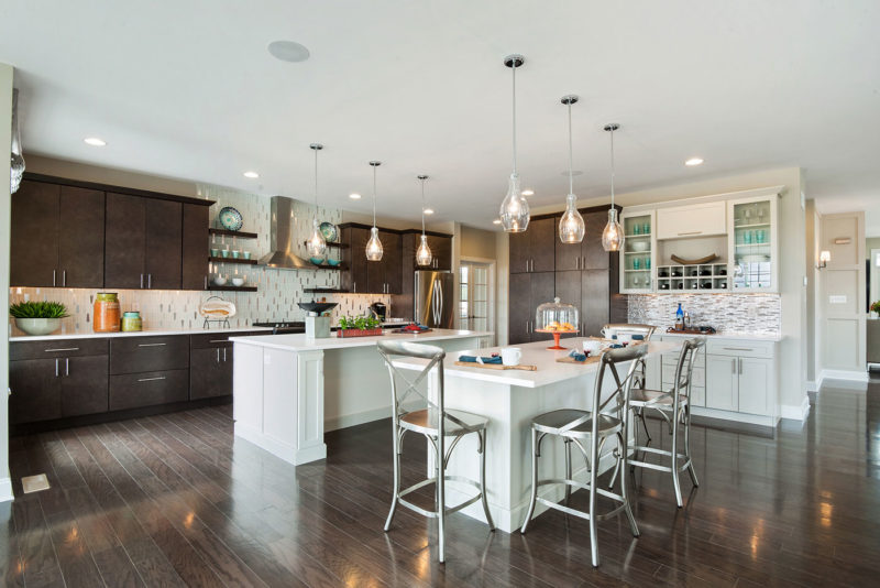Model home kitchen designed with beautiful hardwood floors, white and dark cabinetry, with dramatic backsplash in New Jersey.