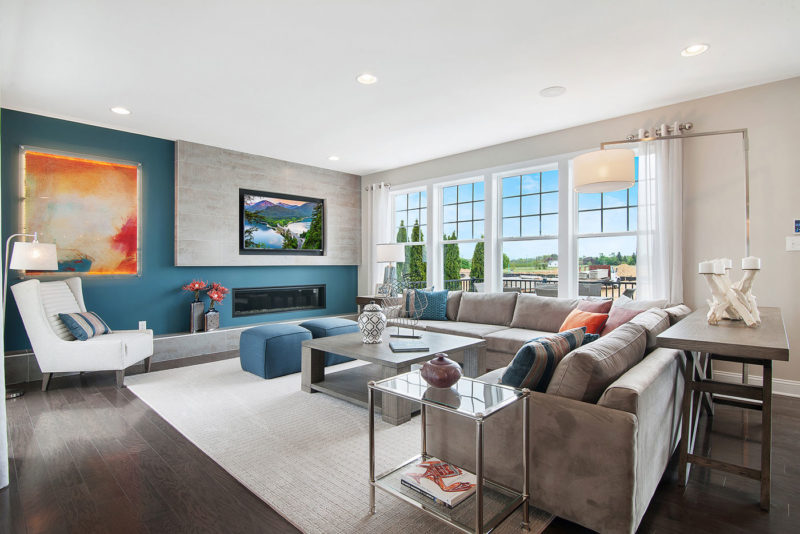 Bright living room designed with blue accent walls and orange backlit art in model home in Glassboro, New Jersey.