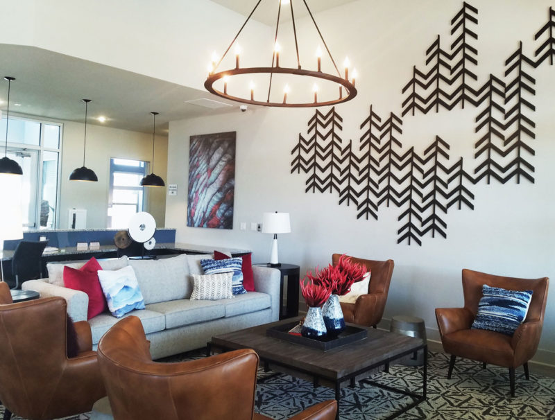 Bright southwestern style sitting area in multifamily clubhouse decorated with large tree-like art in Colorado.