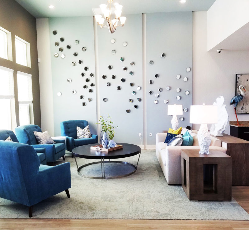 Multifamily clubhouse sitting area with beachy blue walls and scattered bubble mirrors in Florida.