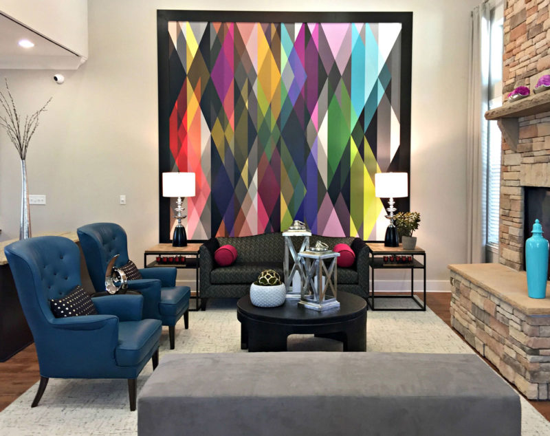 Bright geometrical patterned wallpaper accenting wall in cozy living room area of multi-family clubhouse in Louisiana.