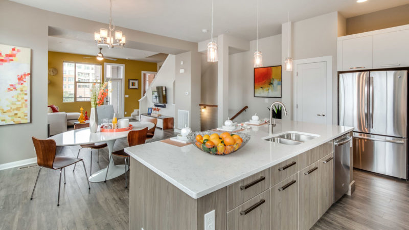 Model home kitchen and dining area designed and merchandised with bright colors and sleek lines in Colorado.