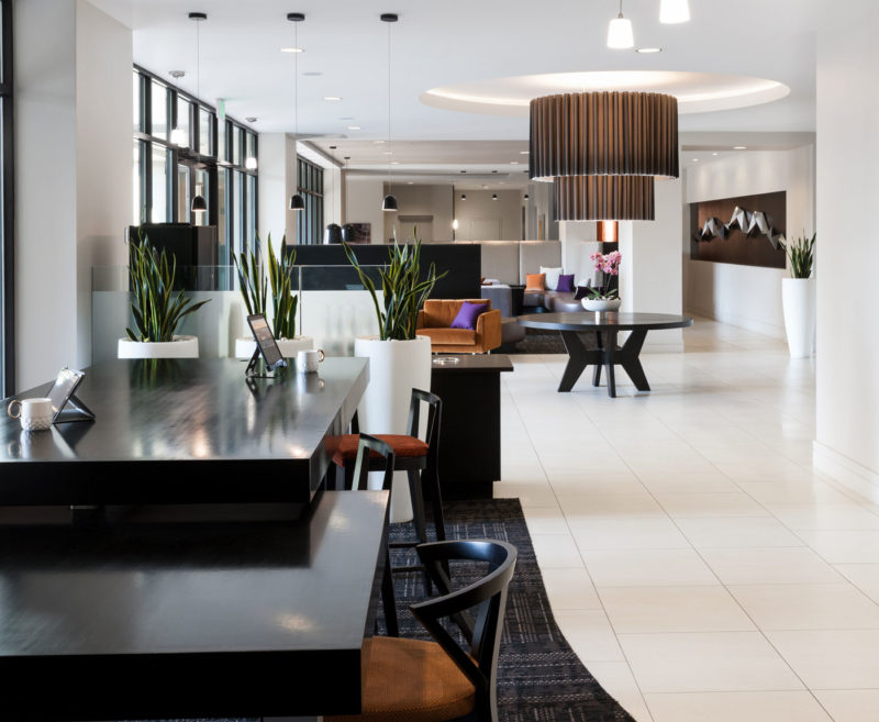 Work stations in apartment merchandised with high-end modern design, white floors and dark wood furniture in Colorado.