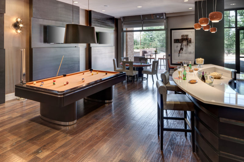 Hardwood floors, wood finishes, pool table, and modern rounded bar in clubhouse of luxury multifamily space in Colorado.