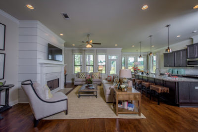 Living room and kitchen in model home with white modern ship-lap fireplace