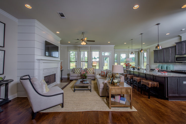 Living room and kitchen in model home with white modern ship-lap fireplace and hardwood floors