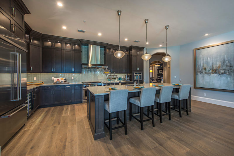 Dark wood updated kitchen with light blue subway backsplash, large island for seating, and hardwood floors in Florida.