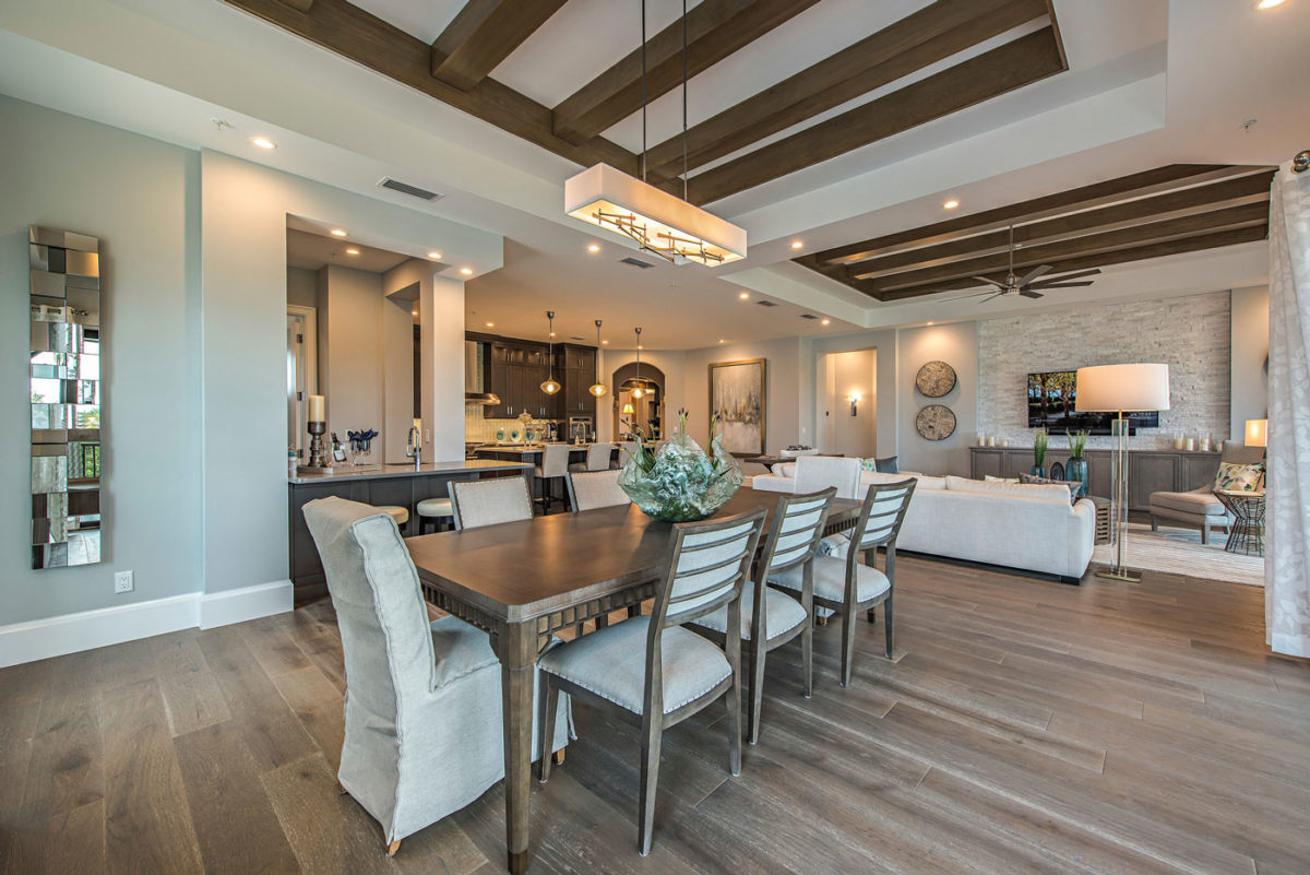 Model home dining, living, and kitchen area merchandised to accentuate exposed wood beams, open floor plan in Naples, FL.