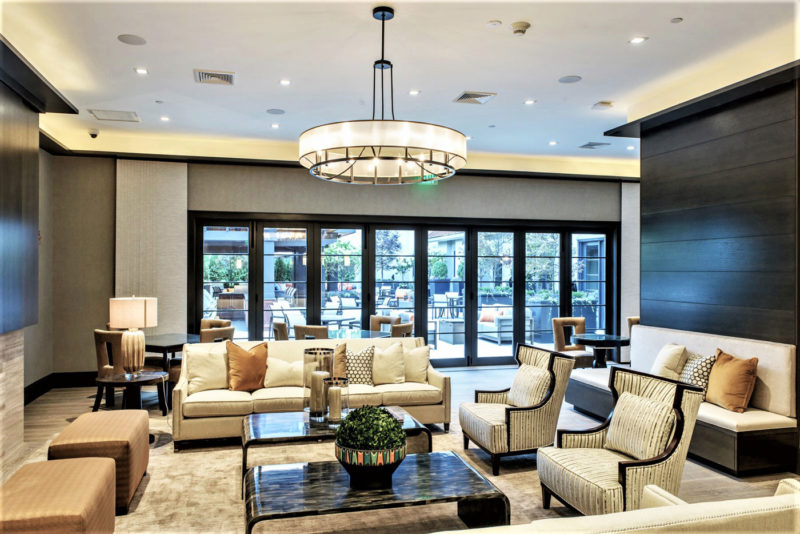 Elegant sitting area with cream sofas, wing-back chairs and colored glass side tables in luxury apartment in New York.