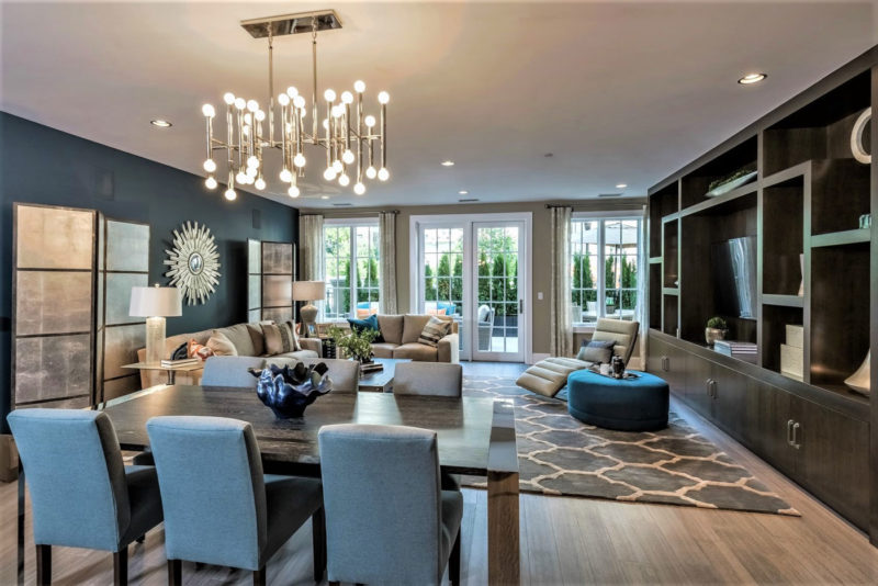 Chic dining and living room area with elegantly merchandised dark wood built-ins and an open floor plan in New York.