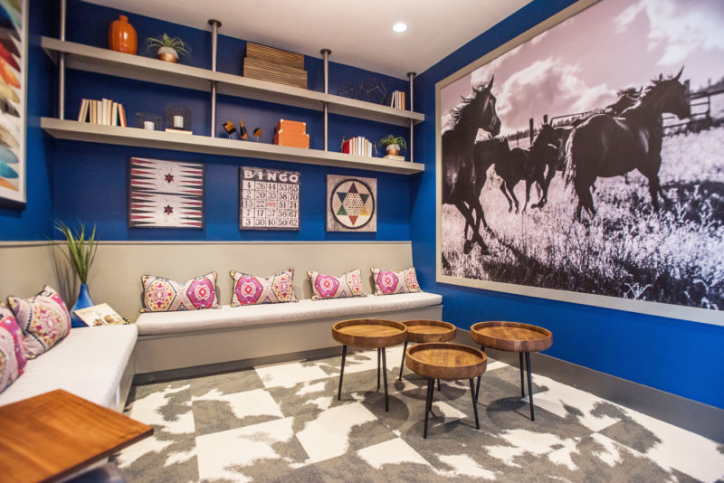 Western-themed lounge room merchandised with cow-print rug, horse mural, games as wall décor, and bright pillows in Colorado.