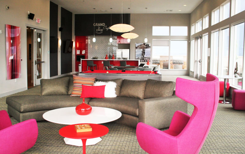 Amenity space designed for younger buyer with mid-century, colorful furnishings and onsite coffee bar in Colorado.