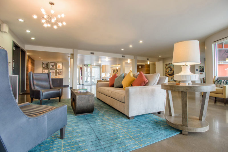 Multifamily clubhouse lounge space with neutral furnishings and bright accents in Denver, Colorado.