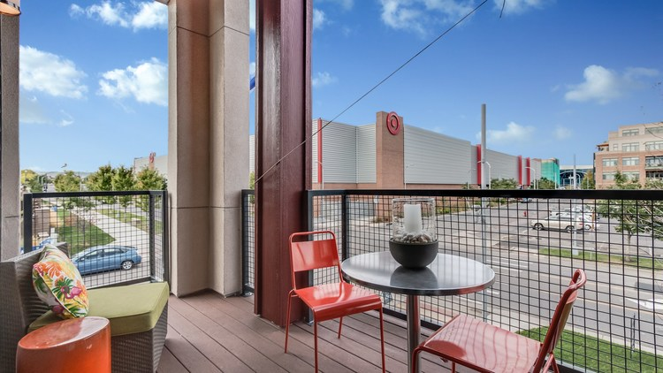 Townhome patio with red metal chairs and table.
