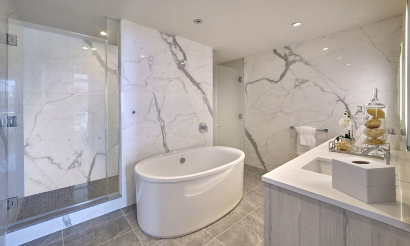 Apartment master bathroom with full white marble walls, oversized shower and upscale finishes in New Jersey.