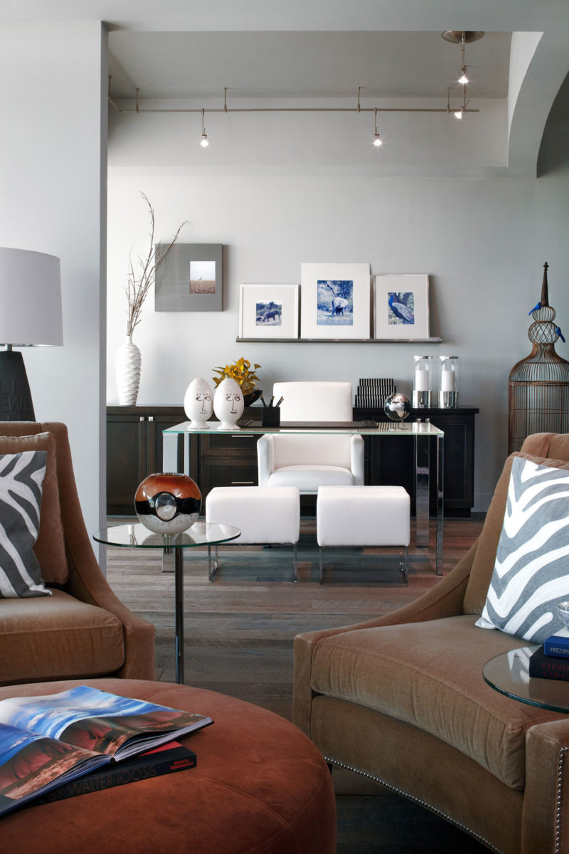 Eclectic modern design of model condo with taupe walls, suede brown chairs, and sleek finishes in Georgia.