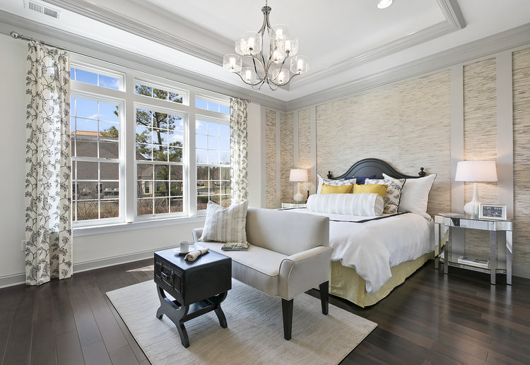 Model home master bedroom with traditional finishes such as crown molding and textured wallpaper
