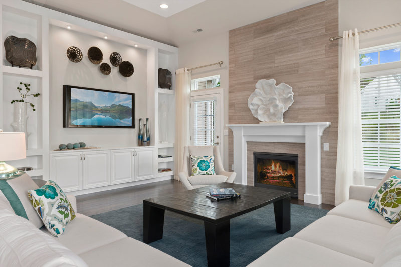 New Jersey model home featuring living room with classic white furniture, pops of blue and a wall length white built-in.