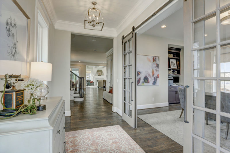 Foyer with sliding grey barn doors into home office and a view of open living area in Colorado model home.