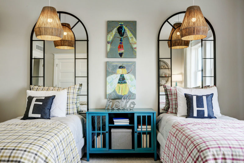 Whimsically designed children's room in model home with bug prints, mirror headboards, and wicker lamp shades in Colorado.
