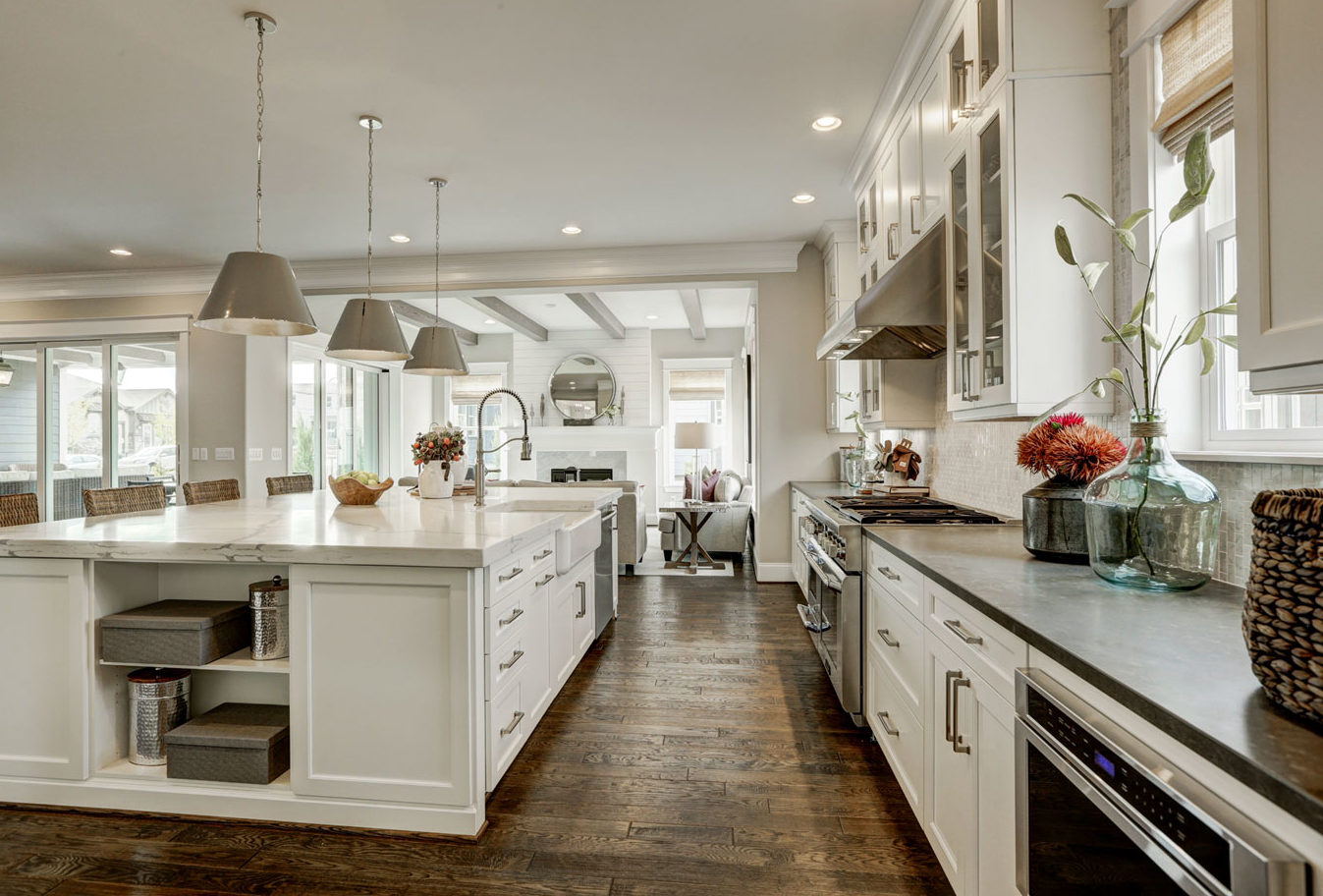 Colorado model home featuring a white farmhouse kitchen with an oversized island and dramatic statement pendants.