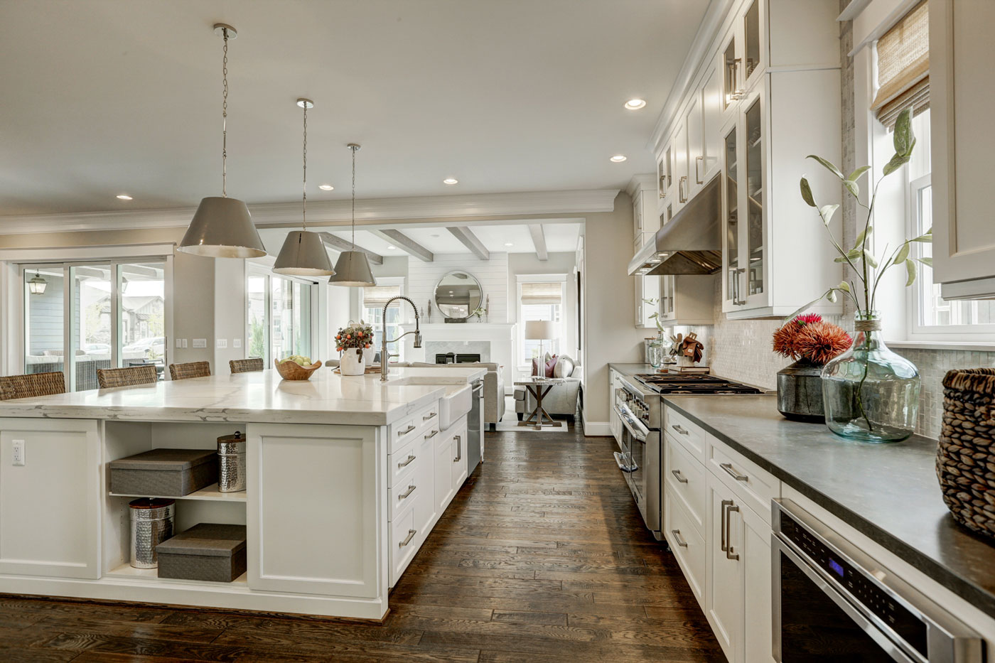 Colorado Model Home Featuring A White Farmhouse Kitchen With An Oversized  Island And Dramatic Statement Pendants