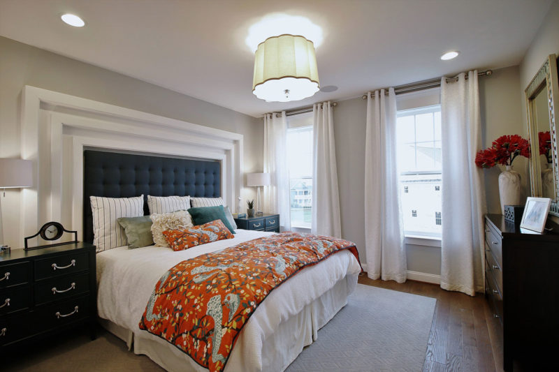 Maryland apartment master bedroom model merchandised with orange bedspread and dramatic upholstered headboard.