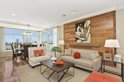 Single family living and dining room with neutral furnishings and wood panel feature wall