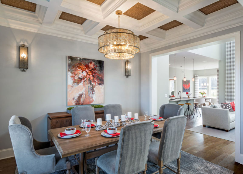 Elegant dining area in model home with dramatic coffered ceiling and open floor plan designed for 55+ home buyer in Delaware.