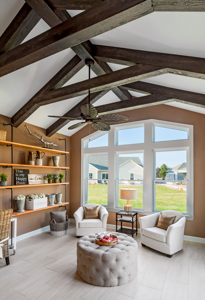 Reading room with vaulted ceiling beam structure, sand colored walls, and light tiled floor in Delaware.