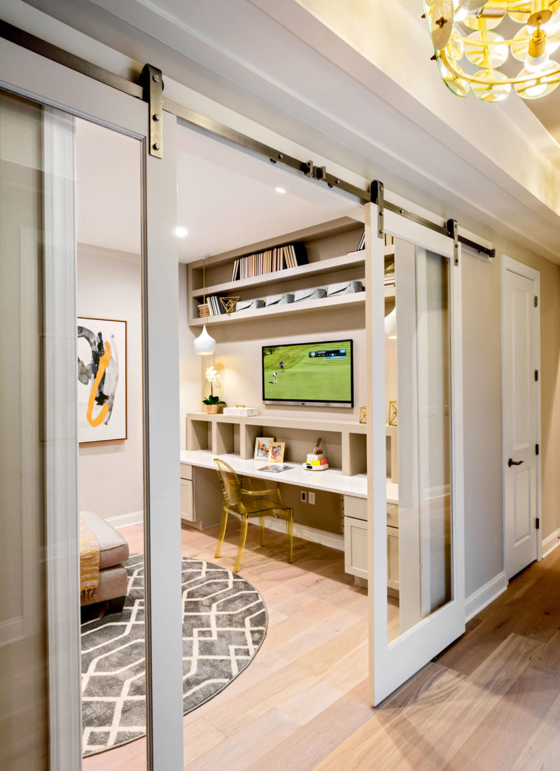 Creatively merchandised flex room with barn door, built-ins, and mobile furnishings in 55+ home buyer model in Delaware.