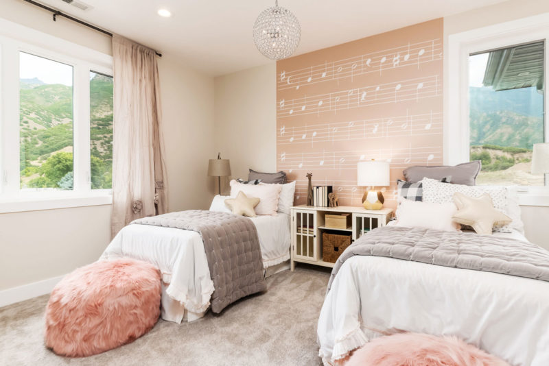 Child's bedroom in Utah model home creatively merchandised with pink and gray patterned musical notes wallpaper.