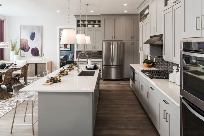 Light gray cabinetry, quartz countertops, and contrasting gray tile backsplash in Utah kitchen.