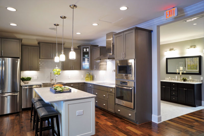 Updated design center with grey cabinets, a white quartz island, and hardwood floors in North Carolina.