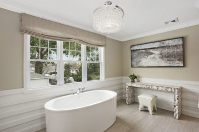 Spacious luxury bathroom with free standing tub, white wainscoting, and bright chandelier