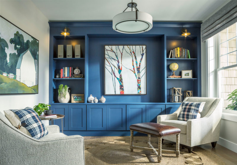 Blue accent wall with built-ins merchandised with comfortable chairs and complimenting finishes for cozy space in Vermont.