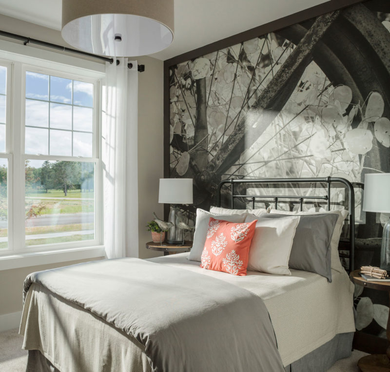 Full wall mural brings outside in and soft gray finishes help create a relaxing bedroom in Vermont model home.