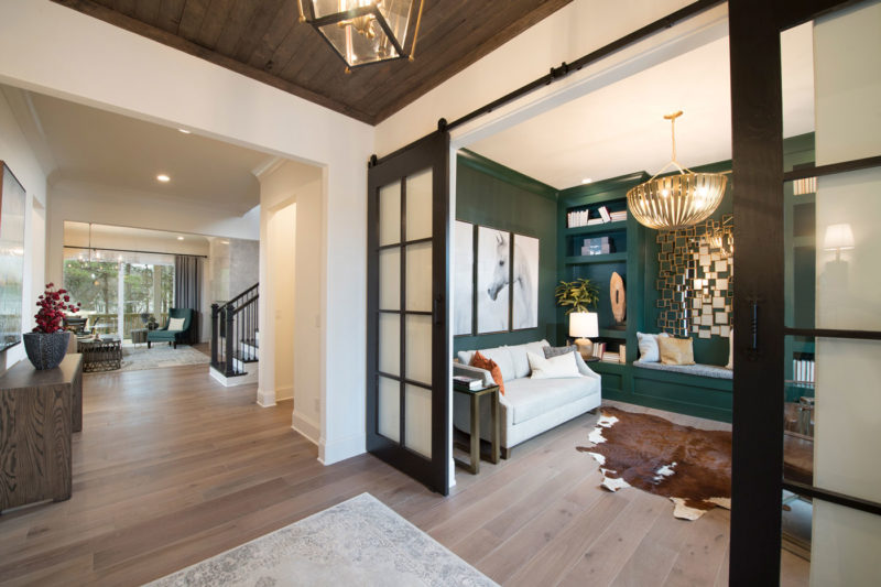 Georgia flex room designed with dark green walls, cow hide rug, horse picture, and contrasting finishes.